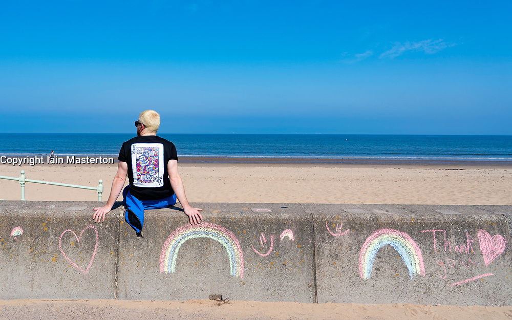 Portobello, Scotland, UK. 25 April 2020. Views of people outdoors on Saturday afternoon on the beach and promenade at Portobello, Edinburgh. Good weather has brought more people outdoors walking and cycling. Police are patrolling in vehicles but not stopping because most people seem to be observing social distancing. Man sitting on seawall beside chalked rainbows. Iain Masterton/Alamy Live News