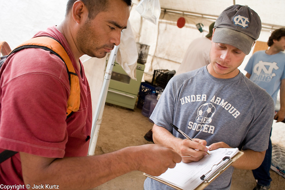 16 JULY 2007 -- NOGALES, SONORA, MEXICO: JOE WILTBERGER (RIGHT), from North Carolina, a volunteer with No More Deaths, interviews a Mexican immigrant deported from the US at the No More Deaths aid station near the Mexican port of entry in Nogales, Sonora, Mexico. No More Deaths and the Sonora state government set up the aid station in 2006 to help Mexican immigrants deported from the US from across the US Border Patrol station in Nogales, Arizona. Volunteers at the aid station provide immigrants, many of whom spend days in the desert before being apprehended by the US Border Patrol, with food and water and rudimentary first aid. The immigrants then go back to their homes in Mexico or into Nogales to make another effort at crossing the border. Volunteers said they help between 600 and 1,000 immigrants per day. The program costs about .60¢ per person to operate. So far this year they've helped more than 130,000 people.  Photo by Jack Kurtz