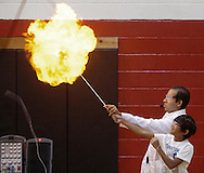 Middletown, New York - Erik Maldonado, rear, helps a camper ignite a hydrogen-filled balloon during a Mad Science demonstration at Middletown YMCA summer camp on Aug. 20, 2010. The string holding the balloon is at left.