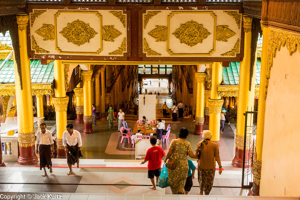 15 JUNE 2013 - YANGON, MYANMAR:  The south stairway into Shwedagon Pagoda. Shwedagon Pagoda is officially known as Shwedagon Zedi Daw and is also called the Great Dagon Pagoda or the Golden Pagoda. It is a 99 meter (325 ft) tall pagoda and stupa located in Yangon, Burma. The pagoda lies to the west of on Singuttara Hill, and dominates the skyline of the city. It is the most sacred Buddhist pagoda in Myanmar and contains relics of the past four Buddhas enshrined: the staff of Kakusandha, the water filter of Koṇāgamana, a piece of the robe of Kassapa and eight strands of hair from Gautama, the historical Buddha. Burmese believe the pagoda was established as early ca 540BC, but archaeological suggests it was built between the 6th and 10th centuries. The pagoda has been renovated numerous times through the centuries. Millions of Burmese and tens of thousands of tourists visit the pagoda every year, which is the most visited site in Yangon. PHOTO BY JACK KURTZ
