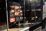 A Londoner walks past the sunlit menu for Angus Steakhouse, now closed during the second lockdown in the second wave of the Coronavirus pandemic, on 6th November 2020, in London, England. This latest government lockdown will last for 4 weeks until at least the 2nd December when only businesses providing essential services and in the case of restaurants, takeaways will be allowed to trade.