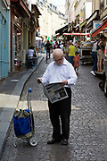 An elderly man reads his  newspaper on the street on the Rue Mouffetard.<br /> Rue Mouffetard is in the Fifth (cinquieme) arrondisement and the street is one of the oldest in Paris. A Roman road, it originally ran from the Roman Rive Gauche city all the way to Italy. Today, the market is famous for it's quality fresh produce and artisanal food shops.