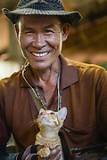 A market porter smiling whilst holding a kitten, Pak Khlong Talat, Bangkok, Thailand