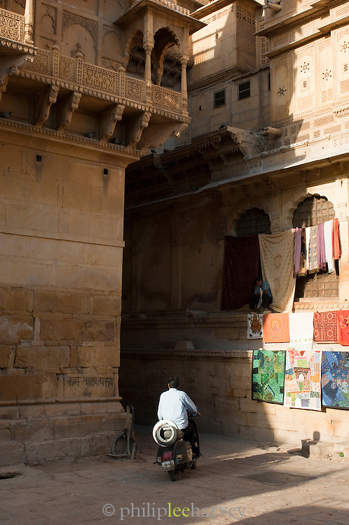 A man driving on a motorbike through Jaisalmer Fort, the 'Golden Fort'. It is one of the largest forts in the world. Jaisalmer, Rajasthan, India