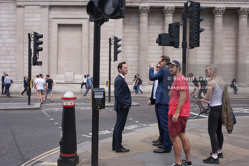 Pedestrians make their way across Threadneedle Street, beneath the tall pillars and columns of the Bank of England, on 4th July, in London, United Kingdom.