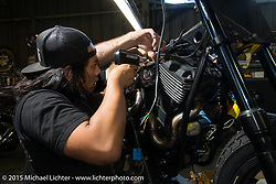 """Aaron Guardado does the finishing touches on wiring during a visit to brothers Shaun and Aaron Guardado's Suicide Machine shop in Long Beach as they finish their """"Speed and Style"""" Street 750 Harley-Davidson for it's debut at Born Free-7. CA, USA. . June 25, 2015.  Photography ©2015 Michael Lichter."""
