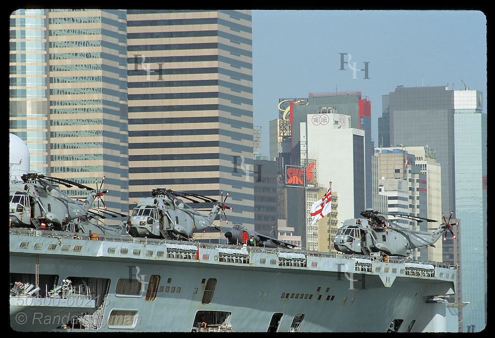 Jets & choppers on British warship contrast with Central District skyscrapers on a sunny day. Hong Kong