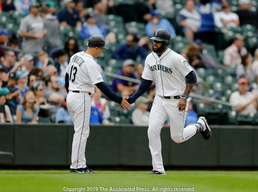 Seattle Mariners' Domingo Santana is congratulated by Chris Prieto after hitting a solo home run on a pitch from Kansas City Royals' Brian Flynn during the seventh inning of a baseball game, Wednesday, June 19, 2019, in Seattle. (AP Photo/John Froschauer)