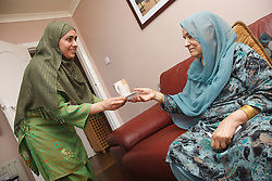 South Asian woman handing tea to mother in law.