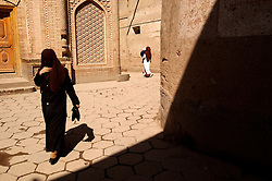 Veiled muslim Uyghur women walking in street of Old Town in Kashgar in Xinjiang China