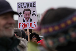 """© Licensed to London News Pictures . 26/01/2014 . Salford , UK . A woman holds a placard with """" Beware Fracula """" around a photograph of Prime Minister David Cameron . Approximately 500 protesters march to an iGas fracking exploration site at Barton Moss , Salford , today (Sunday 26th January 2014) . They walk along the A57 road , blocking traffic as they do . A long term protest camp has been established on an access road leading to the site and today (26th January) protesters from other areas of the country travelled to the site to join with other protesters against fracking . Photo credit : Joel Goodman/LNP"""