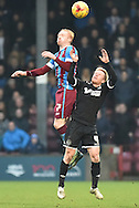Luke Williams of Scunthorpe United and David Perkins of Wigan Athletic go for the ball during the Sky Bet League 1 match between Scunthorpe United and Wigan Athletic at Glanford Park, Scunthorpe, England on 2 January 2016. Photo by Ian Lyall.