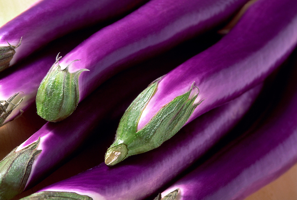 Close up photo of a group of Chinese Eggplants on a table.