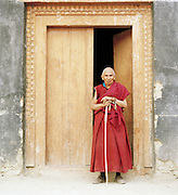 Mature monk in a monastery doorway, Ladakh, India