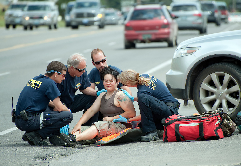 PRICE CHAMBERS / NEWS&GUIDE<br /> Jackson Hole Fire/EMS treats a bicyclist after she collided with a SUV on Tuesday near the Shell gas station. The cyclist was reportedly south-bound on Broadway's sidewalk when the accident occurred.