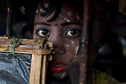 A girl wearing traditional makeup looks from her home during a heavy downpour in Kutupalong, part of the refugee camp sheltering over 800,000 Rohingya refugees, Cox's Bazar, Bangladesh.