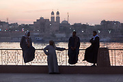 Local men on the West Bank of the river Nile talk at dawn on railings overlooking the city of Luxor, Nile Valley, Egypt. The waterfront is a meeting place to talk business or meet other commuters and from where the state-run ferry plies this great African river. In the distance are the twin spires of the Christian Manak church. (Photo by Richard Baker / In Pictures via Getty Image).