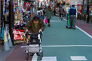 An older woman uses a mobility aid while walking in a shopping street in Shimo-Takaido, Tokyo, Japan. Friday January 11th 2019