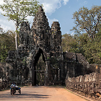 """The three face-towers of the South Gate of Angkor Thom. The left side of the road is guarded by 54 guardian gods, also called """"devas"""" and the right side by 54 demon gods, also called """"asuras""""."""