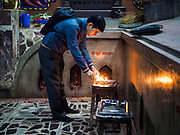07 MARCH 2017 - KATHMANDU, NEPAL: A man lights prayer candles at the Kamaladi Ganesh Temple, the most important Hindu temple dedicated to Ganesh, known as the overcomer of obstacles, in Kathmandu. In Hindu theology, Tuesdays are the best day to pray to Ganesh and the temple is very busy on Tuesdays. People frequently visit temples dedicated to Ganesh when they buy a new home or start a new job.     PHOTO BY JACK KURTZ
