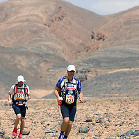 26 March 2007:  #421 Kai Horschig of Germany (right) and #520 Jocelyn Larabie of Canada (left) run across a very rocky plain during the second stage (21.7 miles) of the 22nd Marathon des Sables between Khermou and jebel El Otfal. The Marathon des Sables is a 6 days and 151 miles endurance race with food self sufficiency across the Sahara Desert in Morocco. Each participant must carry his, or her, own backpack containing food, sleeping gear and other material.