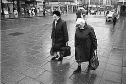 Two elderly women walking along street in the rain carrying shopping,