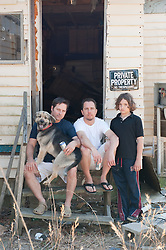 Two men, a dog and a boy sitting on steps of a rundown home