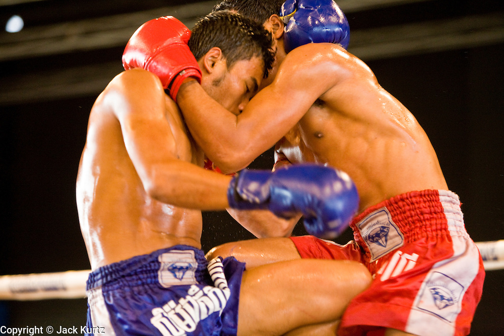 02 JULY 2006 - PHNOM PENH, CAMBODIA: Boxing action during a traditional Khmer boxing match in Phnom Penh, Cambodia. Khmer boxing is the same sport as Muay Thai (traditional Thai kick boxing) but because off animosity between Thailand and Cambodia it is called Khmer Boxing in Cambodia. The Cambodians claim to have invented the sport, which is also practiced in Laos and Burma. Photo by Jack Kurtz