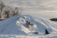 Children play on a mound of snow in a remote village in the Alaskan interior.