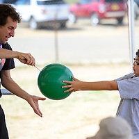 072513  Adron Gardner/Independent<br /> <br /> Mysto the Magi, left, punctures a balloon without it popping in the hands of Madison Toledo in a magic show at the Youth Conference in Crownpoint Thursday.
