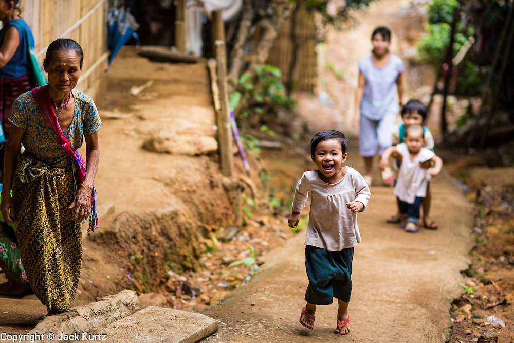 22 MAY 2013 - MAELA REFUGEE CAMP, TAK, THAILAND: Children run up a hill lined with homes in Mae La Refugee Camp. Mae La (Maela) is the largest refugee camp for Burmese in Thailand. Over 90% are ethnic Karen. It was established in 1984 in Tha Song Yang District, Tak Province in the Dawna Range area and currently houses 40,000 refugees. The Thai government has indicated that it would like to close the camp and repatriate the refugees to Myanmar as soon as the political situation in Myanmar is stable enough.   PHOTO BY JACK KURTZ