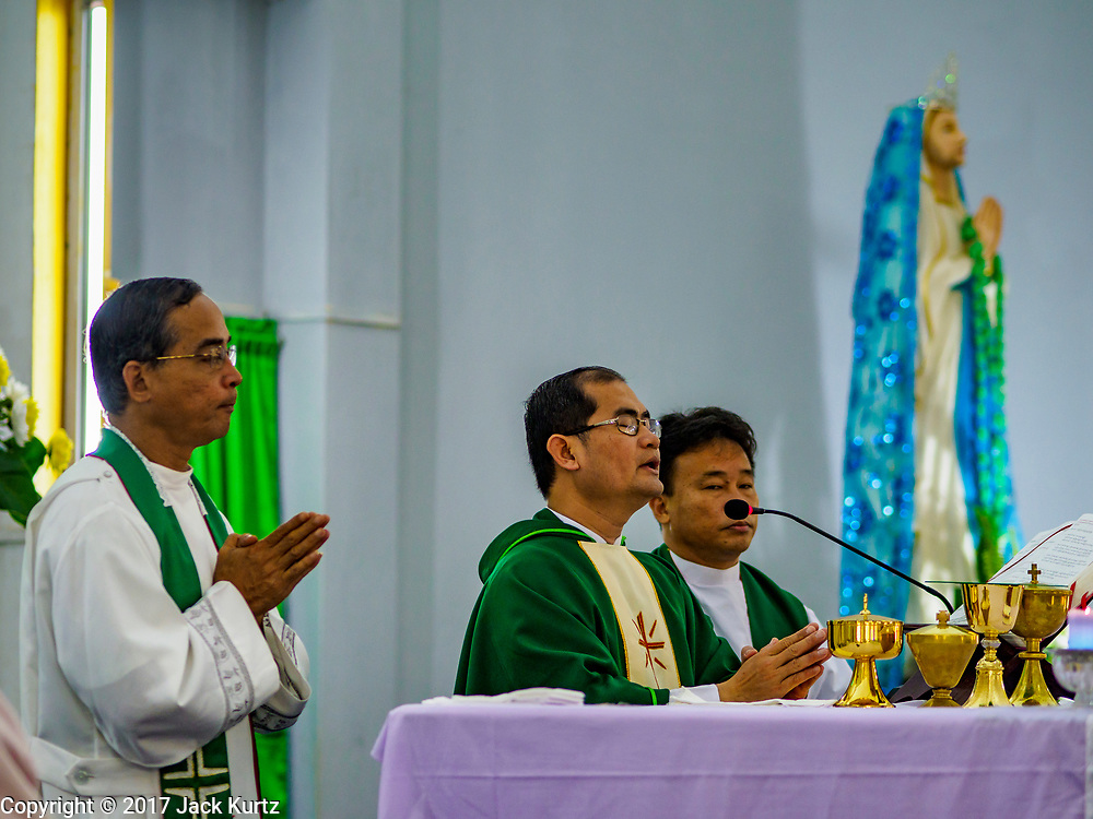 19 NOVEMBER 2017 - HWAMBI, YANGON REGION, MYANMAR: Fathers NOEL LATT (left), JEROME KYI (center) and JOHN LEE celebrate mass at Sacred Heart's Catholic Church in Hwambi, about 90 minutes north of Yangon. Catholics in Myanmar are preparing for the visit of Pope Francis. He is coming to the Buddhist majority country November 27-30. There about 500,000 Catholics in Myanmar, about 1% of the population. Catholicism was originally brought to what is now Myanmar more than 500 years ago by Portuguese missionaries and traders.    PHOTO BY JACK KURTZ