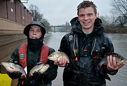 © London News Pictures. 28/02/2014. Worcester, UK.  Two member of the Environment Agency holding roach fish rescued after being trapped on Worcester racecourse when flood waters subsided. Fish, including roach, perch, bream and pike, some weighing over 10lbs, were caught using a large hand net. Photo credit: LNP