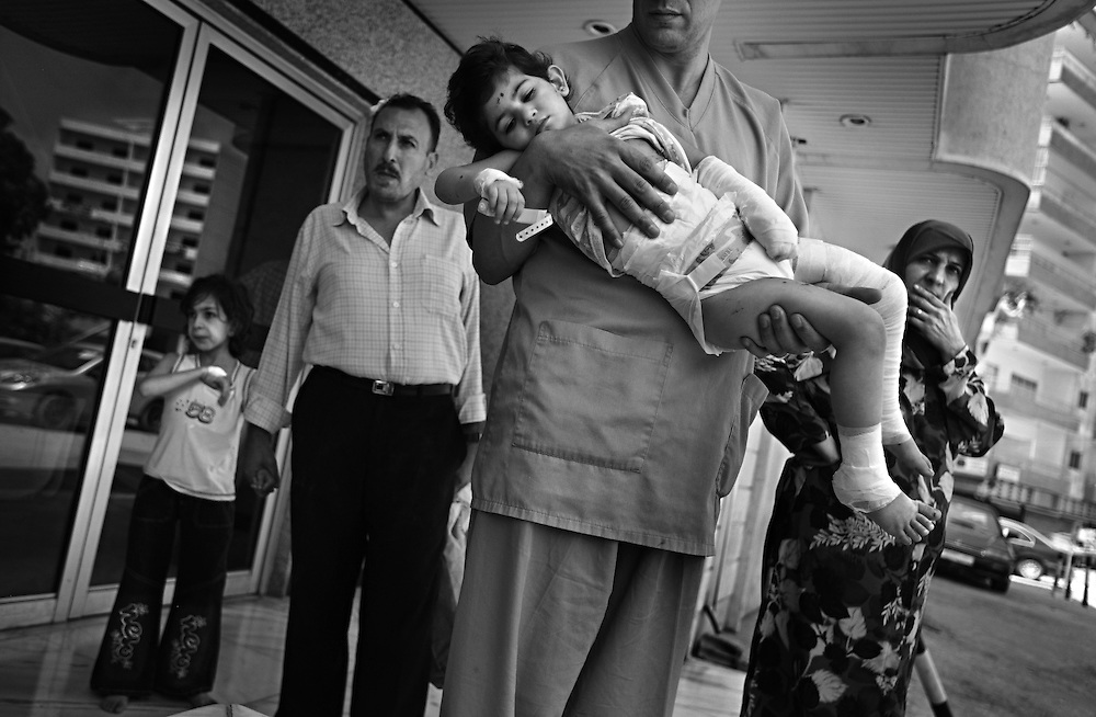 Batool Al Aoun , 6, and Zahraa Al Aoun, 9, are released from the hospital after being treated for wounds sustained when Israeli warplanes leveled a six-story building near their home in Lebanon, July 27, 2006. Neighbors claim several civilians lie crushed beneath the rubble, although some say that building was used to house weekly Hezbollah meetings.