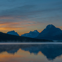 Mist rises over Bow Lake as dawn breaks on Mount Andromache, Mount Hector and Bow Peak in Banff National Park, Alberta, Canada.