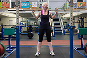 Partially-sighted skiing paralympian from the Sochi Olympics, Kelly Gallagher trains in the gym at the Sports Institute, University of Ulster, Northern Ireland, UK. Using an empty barbell to practice reps, she starts a new training regime for the forthcoming winter season. Kelly Marie Gallagher, MBE is a Northern Irish skier and the first athlete from Northern Ireland to compete in the Winter Paralympics. Gallagher won Britain's first ever Winter Paralympic gold medal during Sochi 2014.