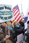 January, 21st, 2017 - Paris, Ile-de-France, France: Women protesters with 'The Majority of Americans did not vote for him, we are sorry' and 'This Pussy grabs back' Placard with Eiffel Tower behindThousands of protesters in Paris join anti-Trump Women's March around the world.