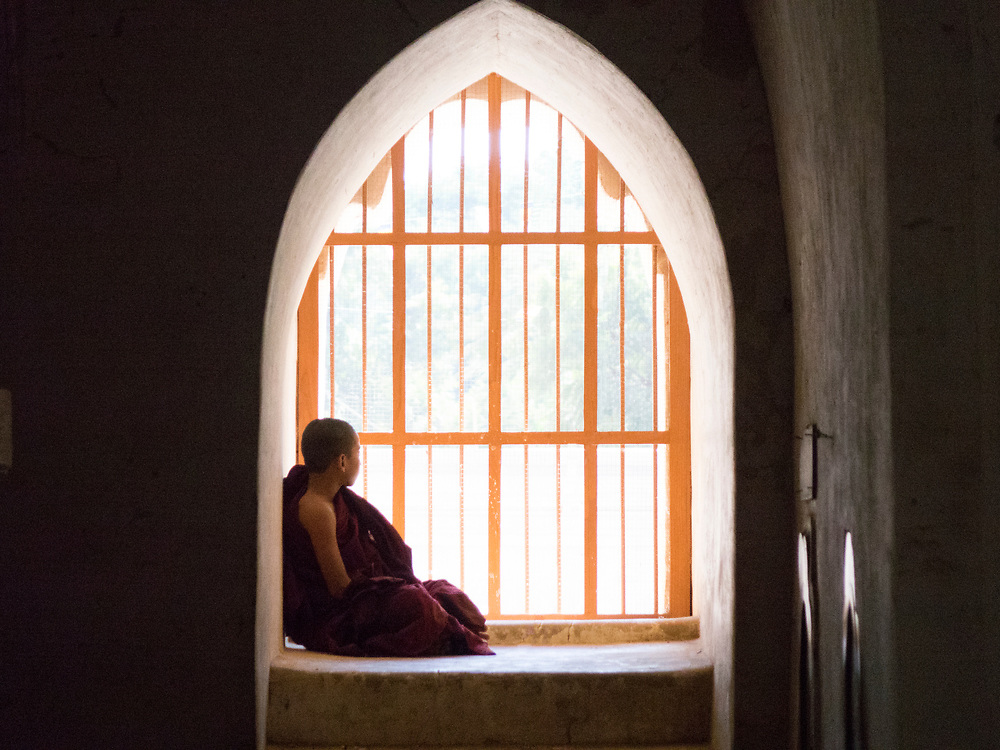 Young monk meditating in one of the arched windows in the Ananda Phaya Temple