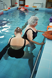 Female physiotherapist working with elderly patient in hydrotherapy pool,