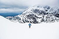 Hiker in winter conditions acending from Torrener Joch pass towards summit of Schneibstein (2276 m),  Hagengebirge, Berchtesgaden Alps, Germany - Austria