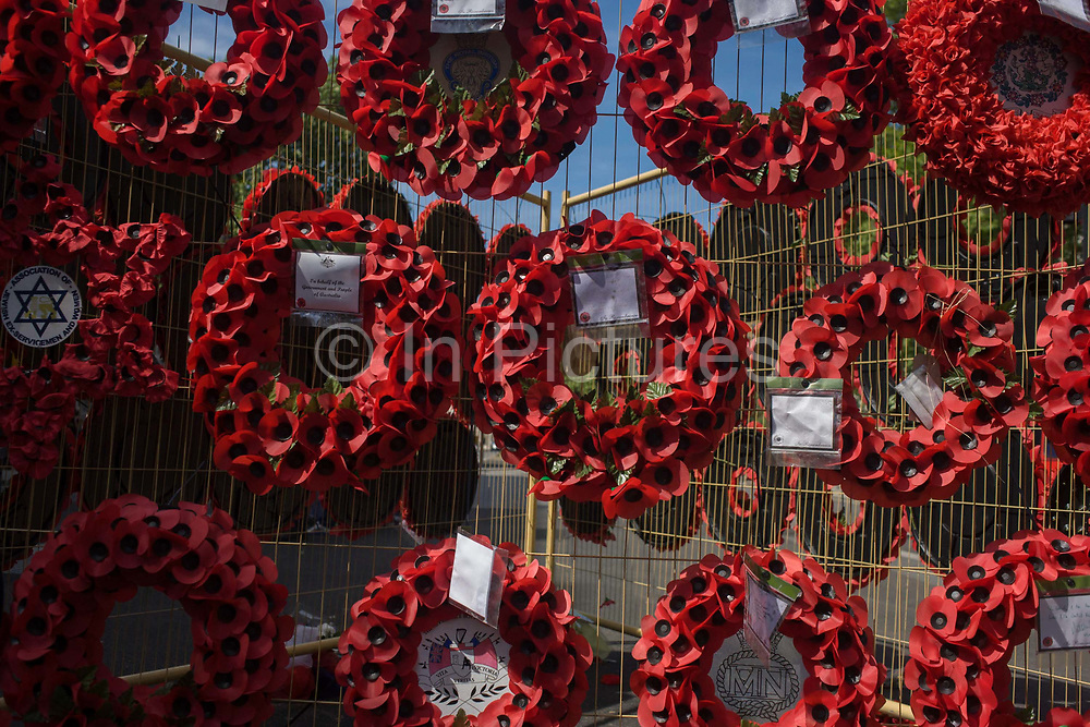 Dedicated to the casualties of wars, red artificial poppies set into wreaths hang on temporary fencing in London's Whitehall. Messages of sympathy from various regiments from around the world are attached to the wreaths which are secured to the metal grills, the red poppies hang in position during a renovation of the nearby Cenotaph, the Edward Luytens-designed memorial to those lost in world wars since WW1 that is the focus of every armistice remembrance ceremony on November 11th.