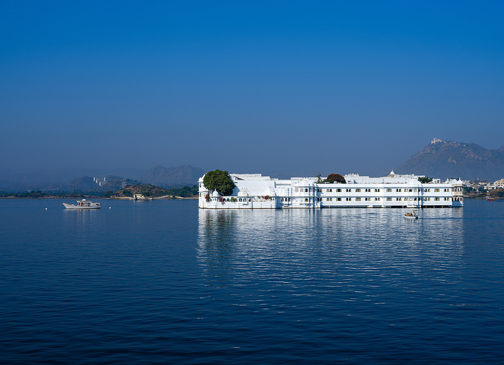 """UDAIPUR, INDIA - CIRCA NOVEMBER 2018:  Lake Palace Hotel formerly known as Jag Niwas in Lake Pichola in Udaipur. The city is the historic capital of the kingdom of Mewar. Surrounded by Aravali Range, which separates it from Thar Desert, and full of lakes Udapiur is also known as the """"City of Lakes"""" and dubbed as the most romantic spot of the Indian Continent."""