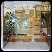 A smashed shop front of a looted shoes shop in Kolokotraoni street, Athens. <br /> <br /> Following the murder of a 15 year old boy, Alexandros Grigoropoulos, by a policeman on 6 December 2008 widespread riots, protests and unrest followed lasting for several weeks and spreading beyond the capital and even overseas<br /> <br /> When I walked in the streets of my town the day after the riots I instantly forgot the image I had about Athens, that of a bustling, peaceful, energetic metropolis and in my mind came the old photographs from WWII, the civil war and the students uprising against the dictatorship. <br /> <br /> Thus I decided not to turn my digital camera straight to the destroyed buildings but to photograph through an old camera that worked as a filter, a barrier between me and the city.