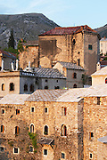 View from the old bridge over the old town. Renovated buildings along the river. Rooftop restaurant with terrasse terasa, other buildings still damaged from the war by bomb shells and grenades. Historic town of Mostar. Federation Bosne i Hercegovine. Bosnia Herzegovina, Europe.