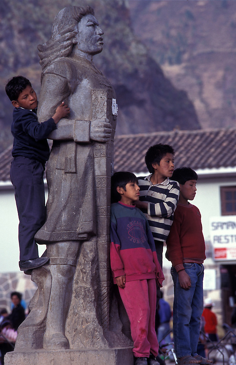 A group of local boys climb the statue of Atahualpa - the last Incan king - to catch a glimpse of the village festival in Pisaq.