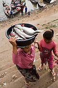 FISHERMEN MEKONG RIVER. South East Asia, Cambodia, Phnom Penh, Mekong River. The Cham fisher people live in various desolated villages along the banks of the Mekong and Tonle Sap rivers. The fisher families live like river gypsy nomads, working and living on their boats, sleeping under a sprung bamboo frame, all their worldly goods stored below deck. They live in extended families, with numerous boats, together for safety. Their diet is rice, vegetables and fish. Their sleek wooden boats are powered by petrol outboard motors with batteries or generators to supply lighting at night. Their fishing technique is laying nets twice or three times per day, which are weighted well below the surface, using old paint aerosal canisters as buoyant floaters, hanging just beneath the surface. These particular fisher families, living at the junction of the Mekong and Tonle Sap rivers, overlooked by Phnom Penh, sell their catch at the Vietnamese market, on the banks of the river. Their life and fortunes are controlled by the cycle of the river. As the river levels drop, so the quantity of fish decreases, until after the heavy floods of the monsoon they fill the river again. They are poor traditional Muslims, marginalised from mainstream society, living a third world life in the immmediate shadow of the first world. The Cham, originally a people of an ancient kingdom called Champa, are a small and disenfranchised community who were disinherited of their land. They are a socially important ethnic group in Cambodia, numbering close to 300,000. The Cham people, live in some 400 villages across Kampong Chnang and Kampong Cham provinces. Their religion is Muslim and their language belongs to the Malayo-Polynesian family. Their livelihoods are as diverse as rice farming, cattle trading, hunting and fishing.///Cham fishermen. Ty Cho and her daughter Baisas go to the Vietnamese market at Phnom Penh to sell their fish and buy fruit for the family
