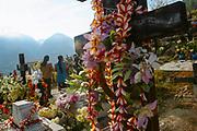 Dos mujeres visitan la tumba de un familiar y ofrecen una corona de flores, al fondo se pueden ver las montañas a las que mas tarde subirán en procesión para realizar un ritual que tiene que ver con el aseguramiento mágico de las lluvias y la fertilidad de las tierras.