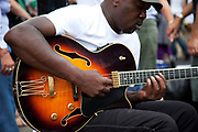 A busker playing the blues on his guitar on Portobello Road market, Notting Hill, West London. This famous Saturday market is when the antique stalls line the streets as well as the food stalls further down the hill. This is classic London with busy crowds of people coming to hang out, maybe buy something, or just browse the stalls and have some food.