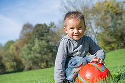 Portrait small boy red football meadow smiling