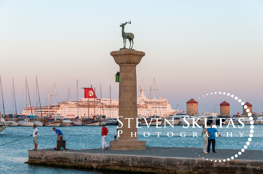 Rhodes. Greece. A column with a deer statue on top stands where a foot of the Colossus of Rhodes was believed to have stood. Two bronze statues (one depicting a stag and the other a doe) stand on columns guarding the Mandaraki harbour entrance where the bronze 35 metre (over 100-feet) Colossus of Rhodes was believed to have stood. Built in 305 BC, the Colossus was one of the Seven Wonders of the Ancient World and depicted the sun god, Helios holding a flaming torch. A violent earthquake in 227 BC caused it to topple over.